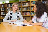 stock photo of tutor  - Student getting help from tutor in library at the university - JPG