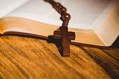 stock photo of rosary  - Open bible with rosary beads on wooden table - JPG