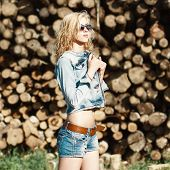 picture of denim jeans  - Portrait of a beautiful woman in sunglasses in denim shorts and jeans jacket on the sawmill - JPG