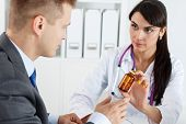 pic of antidepressant  - Beautiful female medicine doctor giving to male patient in business suit jar of pills - JPG