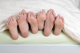 foto of titillation  - Three pairs of feet in bed mixed up - JPG