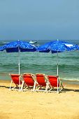 sea beach with chairs on gold sand