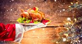Christmas Holiday dinner. Santa Claus hand holding roasted Chicken. Christmas and New Year food conc poster