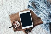 Winter homely scene, scandinavian style. Warm knit sweater, tablet pc with blank screen and cup of s poster
