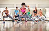 Pretty fitness trainer show aerobic exercises to fitness group poster