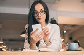 Pretty Young Woman In Eyeglasses Using Smartphone At Table With Coffee Cup In Cafe poster