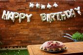 Birthday Party With Pink Birthday Cake On A Wooden Background And Inscription Happy Birthday. poster