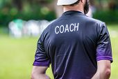 Back View Of Male Soccer Or Football Coach In Dark Shirt With Word Coach Written On Back, Standing O poster