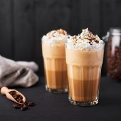Iced Caramel Latte Coffee In A Tall Glass With Chocolate Syrup And Whipped Cream. Dark Wooden Backgr poster