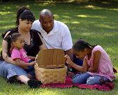 foto of family fun  - Child peeking into picnic basket with her bi - JPG
