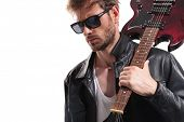 portrait of sexy guitarist with sunglasses looking down to side while holding his electric guitar on poster
