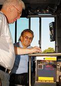 Senior rider storten zijn bus tarief terwijl het stuurprogramma kijkt.