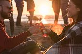 Young Couple enjoying with friends Around Campfire on The Beach At sunset drinking beer poster
