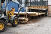 Forklift Truck Grabs Wood In A Wood Processing Plant. Large Log Loader Unloading A Log Truck In The  poster