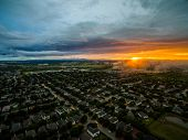 Aerial Drone View Above Suburb Neighborhood Thousands Of Homes And Houses On Ominous Sunset With Fog poster