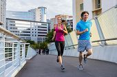 Happy man and beautiful woman jogging together city bridge. Healthy couple running on the city stree poster