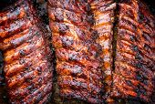 Barbecue spare ribs St Louis cut with hot honey chili marinade as top view copy space and food textu poster