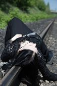 Young gothic girl lying on a railway