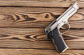 Single Metal And Glossy Pistol On Old Rustic Wooden Weathered Planks poster