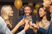 Group of young multiethnic friends toasting with champagne flutes to celebrate new year. Happy guys  poster