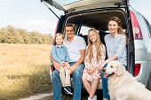 Smiling Young Family With Retriever Dog Sitting In Car Trunk And Looking At Camera In Field poster