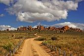 Landscape - Dirt Road In Mountains To Yellow Red Rocks Under Blue Sky With Clouds