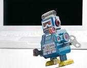 ordenador portátil y viejo juguete robot retro