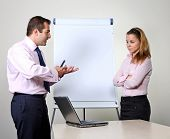 Two office workers, a man giving a presentation on a flip chart trying to convince his female colleague