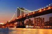 New York City Manhattan Bridge over Hudson River with skyline after sunset night view illuminated wi