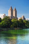 New York City Central Park urban Manhattan skyline with skyscrapers and trees lake reflection with b