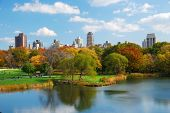 New York City Central Park in Autumn with Manhattan skyscrapers and colorful trees over lake with re