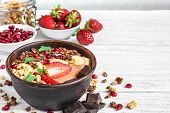 Chocolate Banana Protein Smoothie Bowl With Granola, Strawberry And Pomegranate Seeds On White Woode poster