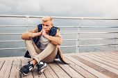 Upset Young Man Sitting By Sea On Pier In Odessa Thinking On Rainy Autumn Day. Depression And Stress poster