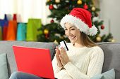 Excited Woman Buying Gifts Online In Christmas Sitting On A Couch In The Living Room At Home poster