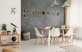 Modern, White Dining Chairs Around A Large Wooden Table In A Botanic Dining And Living Room Interior poster