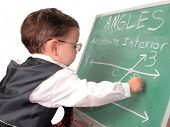 Adorable child prodigy at chalkboard doing math equations for school.  Dressed in suit with glasses.