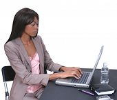 Beautiful African American woman in business attire working on a laptop computer.