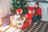 Merry Christmas And Happy New Year. Attractive Picture Of Cute And Nice Family. They Decorating Chri poster