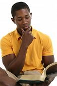 Attractive young man reading book.  Wearing yellow short sleeve shirt and khaki shorts. Shot in studio over white.