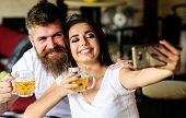 Couple In Love On Date Drinks Beer. Best Friends Or Lovers Drinking Beer In Pub. Take Selfie Photo T poster