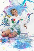 Beautiful young woman sitting in paint covered studio.  Paint splattered on walls, floor, model.  Sh