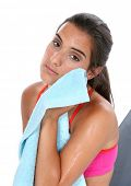 Beautiful teen girl in workout clothes wiping face with towel after workout.  Sitting on workout ben