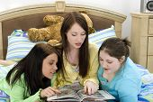 Three teen girls looking through the school yearbook.  At sleep over, wearing pajamas.