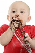 Adorable baby girl licking the mixer full of chocolate batter.  Covered in flour.
