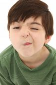 Funny seven year old french american boy making sneeze or nose tickle face.