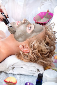 picture of mud pack  - Applying mud face pack on woman face with brush - JPG