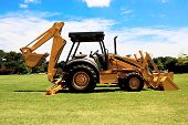 stock photo of backhoe  - Yellow backhoe parked on grass lawn with bucket up - JPG
