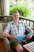 stock photo of average man  - mature man sits on a balcony of tropical hotel with the magazine - JPG