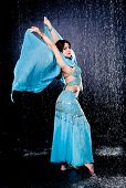 stock photo of dancing rain  - girl executes east dance in the rain against a dark background - JPG