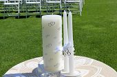 stock photo of unity candle  - Pretty unity candle covered with intertwined hearts on a lace covered table - JPG